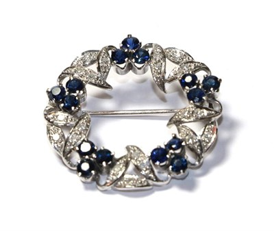 Lot 57 - A sapphire and diamond brooch, realistically modelled as a wreath, clusters of three round cut...