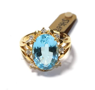 Lot 60 - An 18 carat gold blue topaz and diamond cluster ring, the oval cut blue topaz within a spaced...