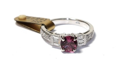 Lot 61 - A tourmaline and diamond ring, the round cut pink tourmaline flanked by trios of baguette cut...