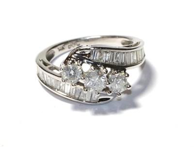 Lot 64 - A diamond three stone twist ring, the graduated round brilliant cut diamonds in white claw...