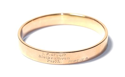 Lot 76 - A bangle, stamped '9CT' and engraved 'I.F. Stuart, Blackruthven, Perth.', measures 6.2cm by 6.5cm