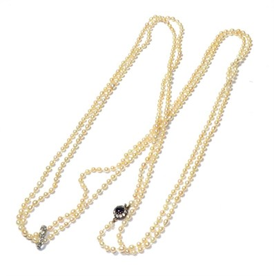 Lot 77 - A seed pearl necklace knotted to a sapphire and diamond cluster clasp with a diamond set...