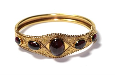 Lot 78 - A garnet hinged bangle, five graduated oval cabochon garnets in yellow rubbed over settings to...