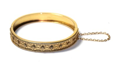 Lot 83 - A 15 carat gold hinged bangle with rope twist decoration, to a plain polished hinged back, measures