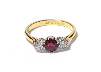 Lot 88 - A ruby and diamond three stone ring, the round cut ruby flanked by round brilliant cut diamonds...