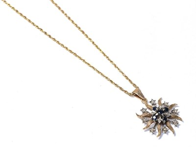 Lot 94 - A sapphire and diamond pendant on chain, the starburst motif set throughout with round cut...