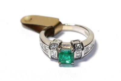 Lot 97 - An emerald and diamond ring, the emerald-cut emerald in a white four claw setting, flanked by a...