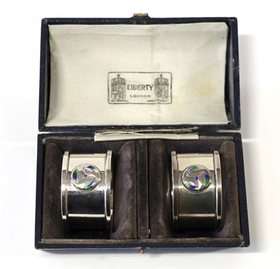 Lot 2068 - A Pair of Arts & Crafts Silver and Enamel Napkin Rings, made by William Hair Haseler, with stylised