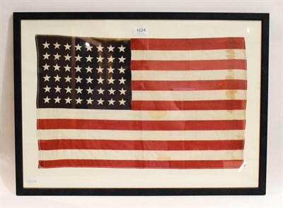 Lot 1024 - A stitched linen flag for the United States of America, 48 stars, 35cm by 57cm, (framed)