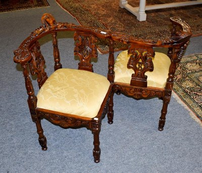 Lot 1066 - A reproduction carved mahogany conversation chair, with drop-in upholstered seats, ornamented...