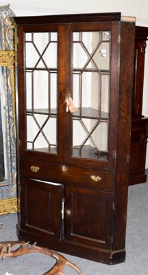 Lot 1091 - A mid 18th century oak free-standing corner cupboard, the moulded cornice above astragal glazed...