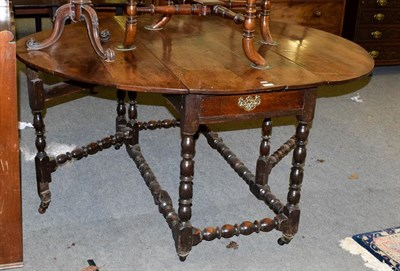Lot 1092 - A joined oak six-to-eight-seater gateleg dining table, circa 1720, with oval drop leaves above...