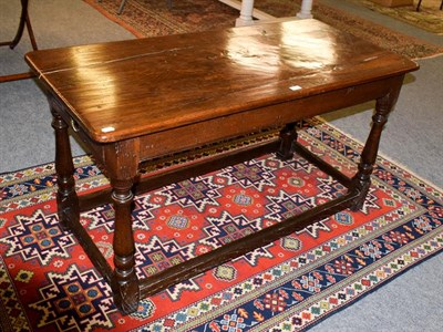 Lot 1094 - A joined oak refectory table, with plain frieze, on turned legs with block feet joined by a...