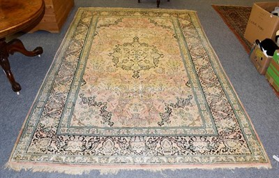 Lot 1100 - Kashmir silk piled carpet, the field with urns issuing flowers around a medallion framed by...