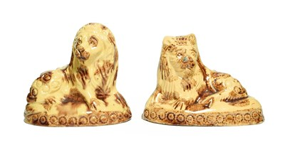 Lot 17 - A Pair of Buff Glazed Earthenware Figures of Lions, circa 1800, recumbent, on oval bases with...