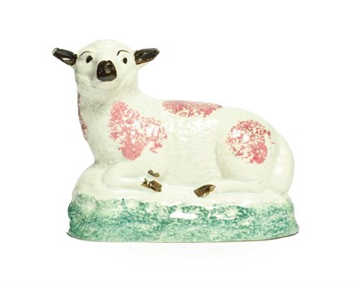 Lot 18 - A Pratt Type Figure of a Sheep, circa 1800, recumbent with puce sponged markings on a green...