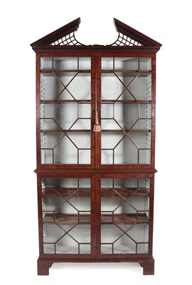 Lot 59 - A George III Mahogany Bookcase, 18th century, the broken arch pediment with trellis panels...