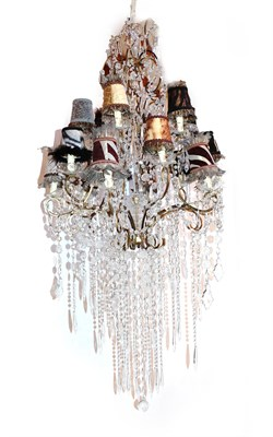 Lot 64 - A Cut Glass and Gilt Metal Eighteen-Light Chandelier, with scroll branches hung with faceted...