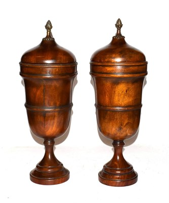 Lot 30 - Theodore Alexander, a pair of modern turned hardwood urns and covers with patinated metal finial's