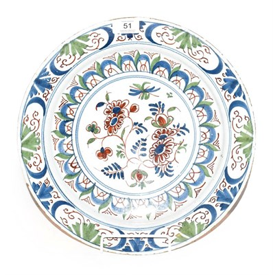 Lot 51 - An English Delft plate, mid 18th century, painted in colours with a central flower spray within...