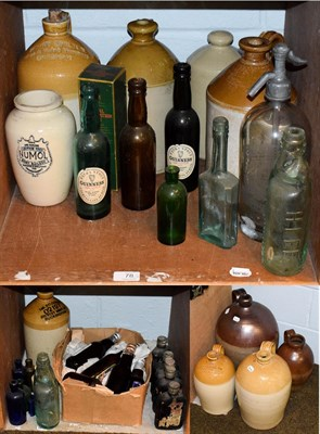 Lot 78 - A quantity of antique glass and stoneware bottles with some advertising examples, including a large