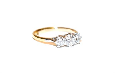 Lot 99 - A diamond three stone ring, the graduated round brilliant cut diamonds in white claw settings, to a
