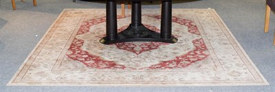 Lot 1071 - A machine made carpet of Oriental design, the brick red field of vines around a medallion...