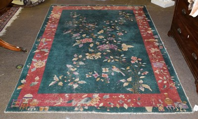 Lot 1073 - Chinese Art Deco rug, the emerald green field with a plant in flower enclosed by meandering...