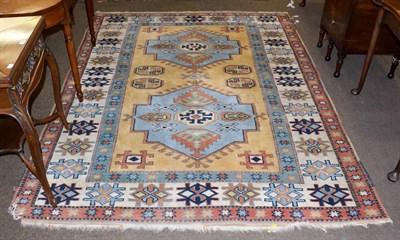 Lot 1078 - A polychrome carpet with a central blue ground medallion, 242cm by 184cm