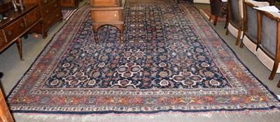 Lot 1079 - A Bidjar carpet, the indigo field with columns of polychrome florwerheads enclosed by madder...