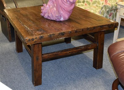 Lot 1095 - A rustic elm plank top coffee table composed of period elements, 93cm by 88cm by 51cm