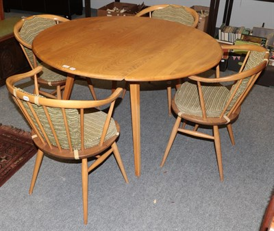 Lot 1054 - A light elm Ercol drop leaf table 123cm by 114cm by 72cm together with four matching horseshoe back