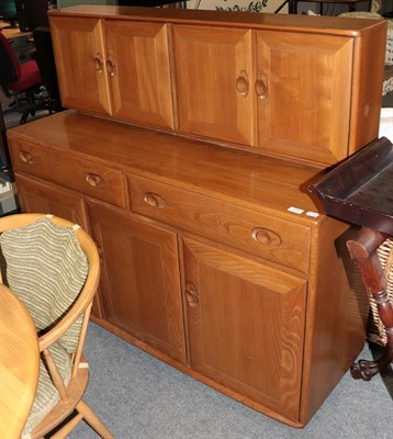 Lot 1055 - A Ercol light elm sideboard 136cms by 47cms by 125cms