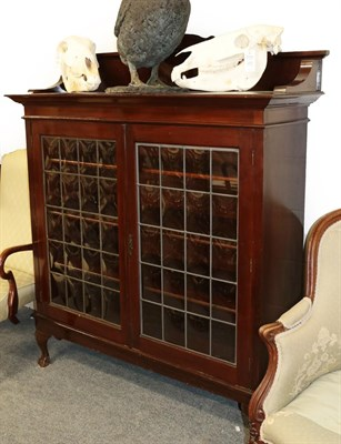 Lot 1070 - An early 20th century glazed bookcase, the leaded doors with shaped glass 140cm by 46cm by 168cm