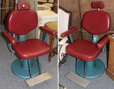 Lot 1075 - A pair of red leather and cast metal barbers chairs