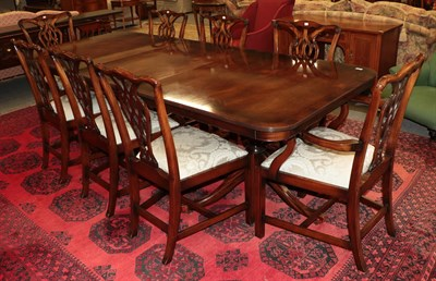 Lot 1094 - A reproduction twin pillar mahogany dining table 245cm by 104cm by 77cm together with a...