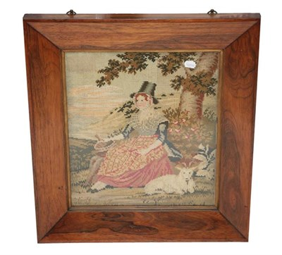 Lot 2058 - 19th Century Wool Work Picture of a Seated Lady in 'Welsh Costume', seated by a tree with a lamb to