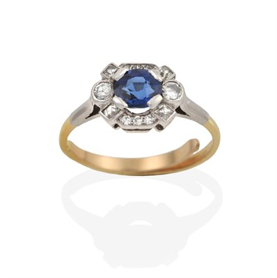 Lot 2000 - A Sapphire and Diamond Cluster Ring, the oval cut sapphire within an undulating border of eight-cut