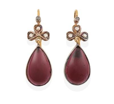 Lot 2003 - A Pair of Garnet and Diamond Drop Earrings, a single rose cut diamond above a trefoil cluster...