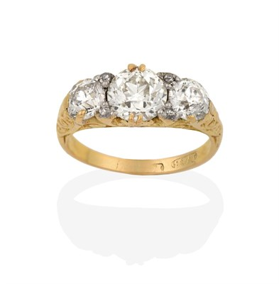 Lot 2004 - A Diamond Three Stone Ring, the graduated old cut diamonds with eight-cut diamond accents, in a...