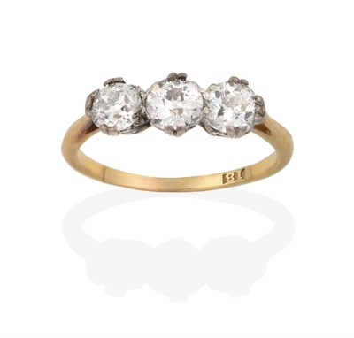 Lot 2006 - A Diamond Three Stone Ring, the old cut diamonds in white double claw settings, to a yellow tapered