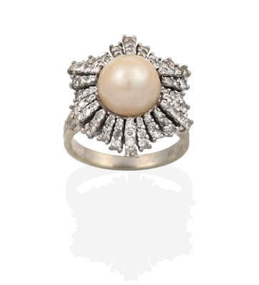 Lot 2007 - A Pearl and Diamond Cluster Ring, the central button pearl within an undulating border of eight-cut