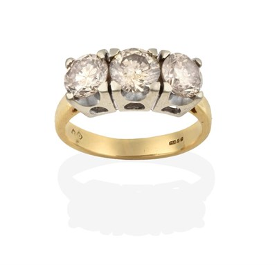 Lot 2013 - An 18 Carat Gold Diamond Three Stone Ring, the round brilliant cut diamonds in white four claw...