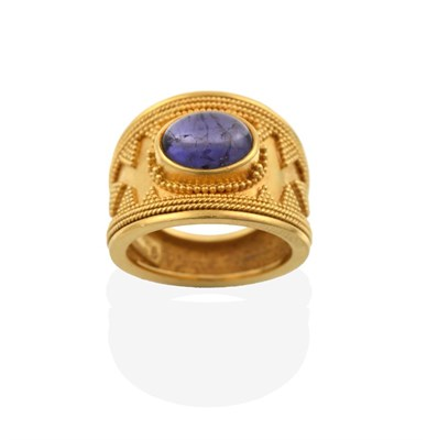 Lot 2053 - An Iolite Ring, possibly by Ilias Lalaounis, the central oval cabochon iolite in a yellow...