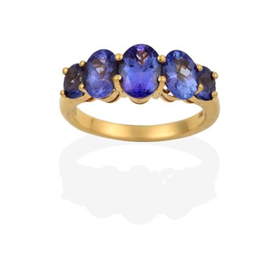 Lot 2061 - An 18 Carat Gold Tanzanite Five Stone Ring, the graduated oval cut tanzanites in yellow claw...