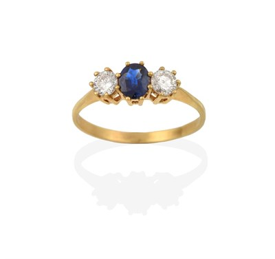 Lot 2063 - A Sapphire and Diamond Three Stone Ring, the oval cut sapphire flanked by round brilliant cut...