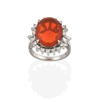 Lot 2064 - A Fire Opal and Diamond Cluster Ring, the oval cut fire opal within a border of eight-cut...