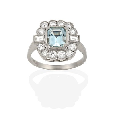 Lot 2065 - An Aquamarine and Diamond Cluster Ring, the emerald-cut aquamarine within a border of round...