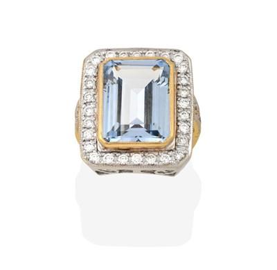 Lot 2076 - An Aquamarine and Diamond Cluster Ring, the emerald-cut aquamarine in a yellow millegrain...