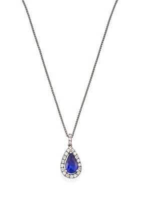 Lot 2079 - An 18 Carat White Gold Sapphire and Diamond Pendant on Chain, the pear shaped sapphire within a...